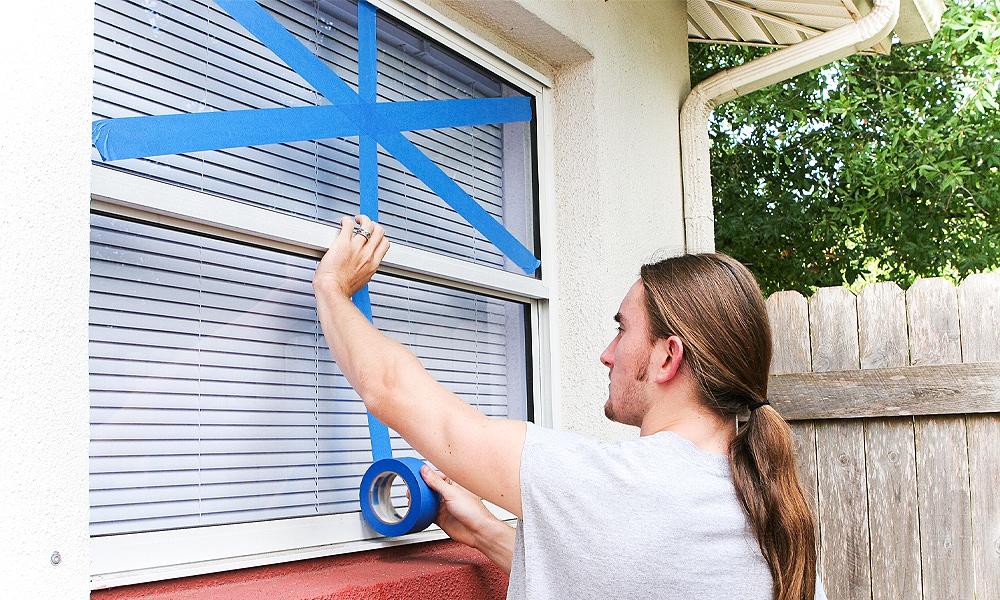 man taping a window