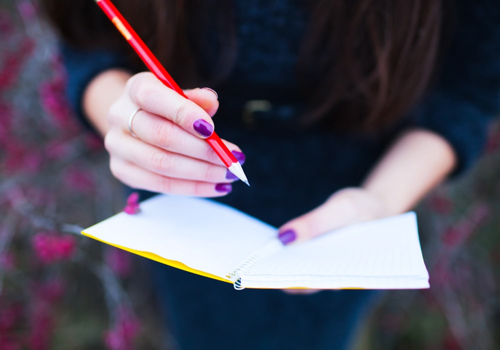 woman writing into a journal